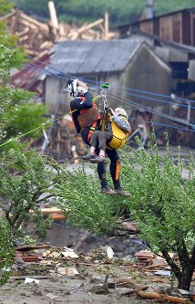 An elderly lady, right, is lifted to safety by a Japan Coast Guard helicopter in Asakura, Fukuoka Prefecture, on July 6, 2017. (Mainichi)