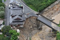 One corner of a house is left hanging in the open air on July 6, 2017 after torrential rain caused the earth beneath it to collapse, in Asakura, Fukuoka Prefecture. (Mainichi)