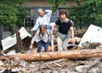 Local residents climb over wood and earth as they escape from an isolated area in the village of Toho, Fukuoka Prefecture, on July 6, 2017. (Mainichi)