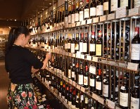 A woman compares French wines at Takashimaya Nihombashi department store in Tokyo's Chuo Ward on July 6, 2017. (Mainichi)