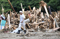 A man walks past rubble on his way to his home in Asakura, Fukuoka Prefecture, on July 11, 2017. (Mainichi)