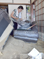 A woman packs clothes at her home in Asakura, Fukuoka Prefecture, which is covered with mud, on July 11, 2017. (Mainichi)