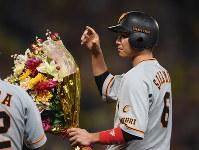 9日の阪神戦の九回表2死一、三塁、左前適時打を放ち、通算1500安打を達成して花束を受け取る巨人の坂本勇=阪神甲子園球場で、久保玲撮影
