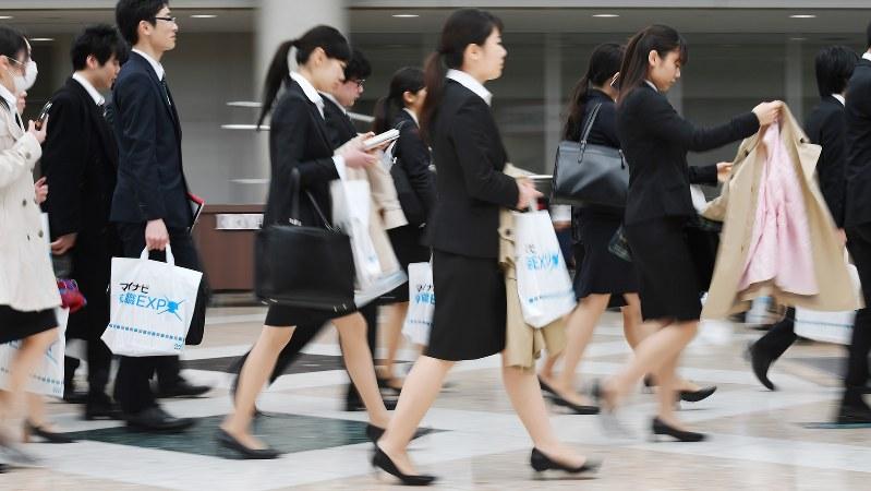 仕事と育児を両立できるか、就職を目指す女子学生は真剣に考えている。写真はリクルートスーツで合同企業説明会に向かう学生たち=2017年3月11日、宮間俊樹撮影
