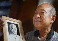 益田さんの80歳のころの写真を手にする三男・遙さん=広島市西区で、山田尚弘撮影
