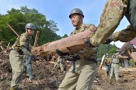Self-Defense Force members clear away driftwood in the Hakimasue district of Asakura, Fukuoka Prefecture, on July 14, 2017, following deadly rains that hit northern Kyushu. (Mainichi)