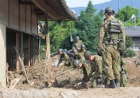 Self-Defense Force members are seen removing dirt from a house in Asakura, Fukuoka Prefecture, on July 14, 2017. (Mainichi)