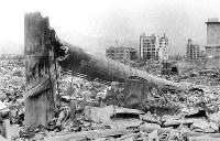 (9)爆心地と反対方向に倒壊した煙突(爆心地から300メートル)。奥の建物は(右から)中国新聞社、福屋新館、福屋旧館=広島市革屋町(現広島市中区本通)で1945年9月11日前後、山上圓太郎撮影 ※広島平和記念資料館(広島原爆資料館)の検証による