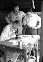 (20)広島第一陸軍病院宇品分院で顕微鏡をのぞくアメリカ陸軍調査団のスタフォード・ウォレン軍医大佐。左に立つのはアメリカ太平洋軍顧問軍医アシュレイ・オーターソン=広島市宇品町(現広島市南区宇品東5)で1945年9月10日前後、山上圓太郎撮影 ※広島平和記念資料館(広島原爆資料館)の検証による