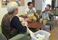 「こうやって伸ばすのよ」と介護スタッフ(中央)に教えながら洗濯物を畳むグループホームの入居者。以前はスタッフがしていた=千葉県船橋市のグループホーム「高根台つどいの家」で、稲田佳代撮影