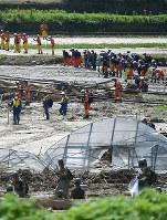 豪雨で土砂が流れ込んだ川で安否不明者の捜索をする消防隊員や自衛隊員ら=福岡県朝倉市で2017年7月16日午前10時40分、三浦博之撮影