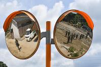 ミラーに映る、川で安否不明者の捜索をする自衛隊員=福岡県朝倉市で2017年7月16日午前9時半、三浦博之撮影