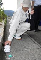 アリ用の殺虫餌(手前)と調査用トラップを仕掛ける敦賀港湾事務所の職員=福井県敦賀市金ケ崎町の敦賀港鞠山南地区国際物流ターミナルで、近藤諭撮影