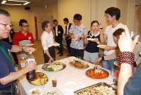 食事を楽しみながら交流する留学生ら