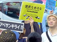 「こんな人たち」と書かれたプラカードを掲げる人たち=東京・新宿で9日、写真は動画から松崎進撮影