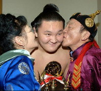 Hakuho receives a celebratory kiss from each of his parents visiting Japan after winning the Technique Prize on the final day of the January Grand Sumo Tournament on Jan. 23, 2005. (Mainichi)