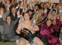 A jubilant Hakuho holds the Emperor's Cup after his first tournament victory, with supporters lined up behind him, including his father Jigjidiin Monkhbat, right, at the Ryogoku Kokugikan sumo venue in Tokyo, on May 21, 2006. (Mainichi)