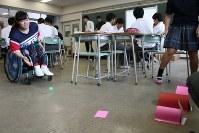 高校生が作った新競技を試す障害者スキー選手の新田のんのさん。色画用紙で作ったトンネルにピンポン球を通し、トンネルの穴の大きさで難易度別に点数を競う=東京都板橋区の都立高島高校で2017年6月8日、中村美奈子撮影
