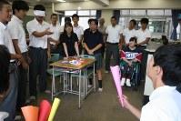 高校生が作った新競技の発表を見る障害者スキー選手の新田のんのさん(後ろから2列目右端)。2人1組で楽しむゲームで、1人は目隠しをして、相手が持つ色画用紙の円すい形の筒にピンポン球を入れる。筒の穴が小さいほど点数が高い=東京都板橋区の都立高島高校で2017年6月8日、中村美奈子撮影