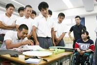 高校生が作った新競技の発表を見る障害者スキー選手の新田のんのさん(右端)。画用紙の坂からピンポン球を落とし、落ちた場所に付いている点数で競う=東京都板橋区の都立高島高校で2017年6月8日、中村美奈子撮影