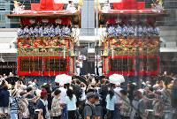 四条通を進む長刀鉾(左)とビルの壁に映り込んだ長刀鉾=京都市下京区で、小松雄介撮影