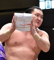 Hakuho holds his prize money with both hands after setting a record of 33 tournament wins at the Ryogoku Kokugikan in Tokyo, on Jan. 23, 2015. (Mainichi)