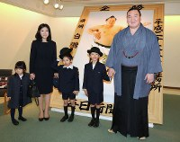 Hakuho, far right, smiles with his family in front of a January 2015 victory photo of himself, in Tokyo's Chiyoda Ward, on April 8, 2015. (Mainichi)