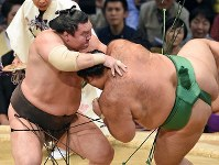 Hakuho, left, throws opponent Kaisei to the ground for his 1,000th career victory, at Fukuoka Kokusai Center in Fukuoka, on Nov. 15, 2016. (Mainichi)