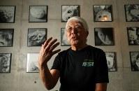 東京アートミュージアムで、作品の前でインタビューに答える比嘉良治さん=東京都調布市で2017年7月8日、小川昌宏撮影