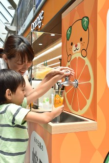 A family pours Satsuma citrus orange juice from a faucet at Matsuyama Airport in Ehime Prefecture on July 20, 2017. (Mainichi)