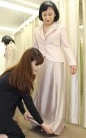 顔映りのいい、ピンクジャガードのジャケットとシャンパンゴールドのドレスを試着する60代の女性。体形に合わせ、お直しも=東京都新宿区の京王百貨店で