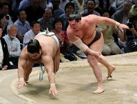 Yokozuna Hakuho, right, pushes Takayasu down onto the clay, recording his 1,048th win and breaking the record for most career wins, at the Nagoya Grand Sumo Tournament on July 21, 2017. (Mainichi)
