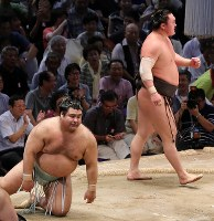 Yokozuna Hakuho, standing, looks triumphant after pushing opponent ozeki Takayasu to the ground in a bout at the Nagoya Grand Sumo Tournament on July 21, 2017. This was Hakuho's 1,048th win, making him the lone record holder for most career wins. (Mainichi)