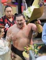 Yokozuna Hakuho shows off bouquets as he leaves the ring after winning against ozeki Takayasu at the Nagoya Grand Sumo Tournament on July 21, 2017. This was Hakuho's 1,048th win, making him the lone record holder for most career wins. (Mainichi)