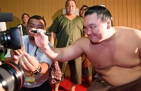 After breaking the record for most career wins at 1,048, yokozuna Hakuho signs his autograph in front of a television camera in his dressing room at Aichi Prefectural Gymnasium on July 21, 2017. (Mainichi)