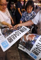 Extra editions of the Mainichi Shimbun reporting Hakuho's record-breaking victory are distributed to passersby in front of JR Shimbashi Station in Tokyo's Minato Ward at around 7 p.m. on July 21, 2017. (Mainichi)
