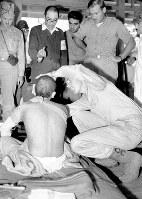 大野陸軍病院で患者を診察する米国マンハッタン管区調査団。中央は東京帝国大の都築正男博士=広島県大野村(現廿日市市)で1945年9月10日、新見達郎撮影