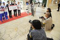 阪急百貨店うめだ本店9階でのNPOフェスティバルを撮影する広報写真ボランティアの3人(黄色や白の腕章)=2017年6月30日、大島秀利撮影