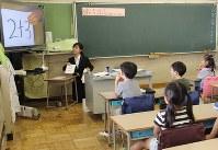授業で大型テレビを使い、計算の練習をさせる教育実習生の河本はるかさん=東京都小平市で