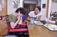 友田英子さん(49) 自分の手でロールパンを食べる=塩田彩撮影