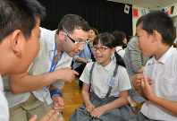A teacher and students play a game at an