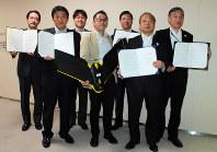 ドローンを手に持つ古橋理事長(中央)と多摩、狛江、調布、稲城、府中、日野の各市長=新宿区の都庁で