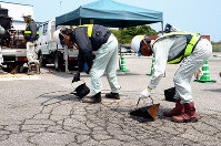 ヒアリの侵入を防ぐためアスファルトを流し込む作業員=高知市仁井田の高知新港で、岩間理紀撮影