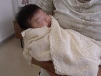 伯州綿で作ったおくるみに包まれスヤスヤと眠る赤ちゃん