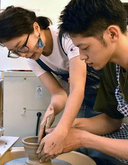 中垣さん(左)の指導を受けながら電動ろくろの体験をする参加者