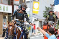 A samurai horseman receives a cup during the kaeri-uma (returning horse) procession, held for the first time in seven years in the Fukushima Prefecture city of Minamisoma, on July 30, 2017. (Mainichi)