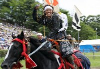 A rider celebrates after finishing first in the Kacchu Keiba race at Hibarigahara festival field in the city of Minamisoma, Fukushima Prefecture, on July 30, 2017. (Mainichi)