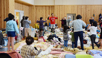 熊本地震の避難所で体操する高齢者や子どもたち。部屋は満杯で、ベッドや仕切りなどはなく、毛布などを敷いて生活した=熊本県益城町で、花澤葵撮影