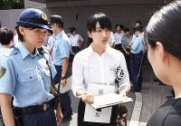 現場対応訓練で、ひったくりの被害女性役(右手前)から事情を聴く参加者(中央)=奈良市の県警察学校で、郡悠介撮影