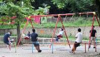 日曜日、公園で子供を遊ばせる父親たち